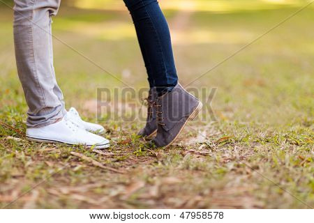 teenage couple kissing outdoors at the park
