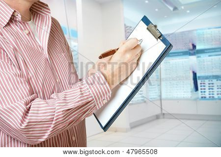 Salesperson in optician store holding a clipboard and taking a notes with pen