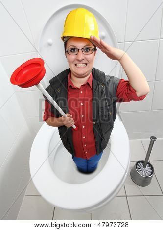 Funny repairman with red toilet plunger cleaning the toilet bowl.