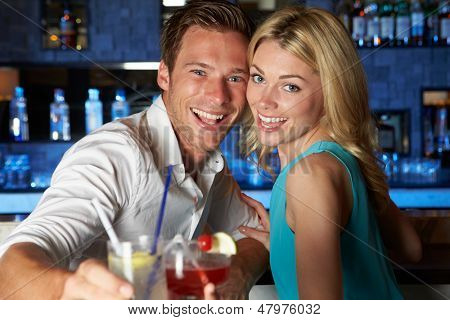 Couple Enjoying Cocktail In Bar
