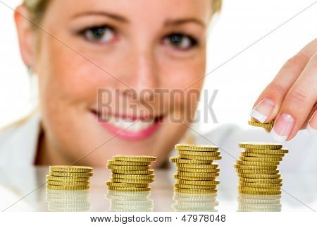 a woman stacks coins. save money for the future.