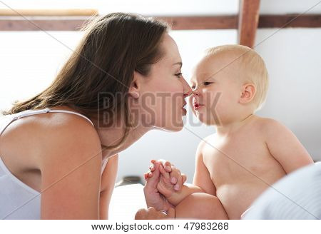 Beautiful Woman And Baby Playing On Bed