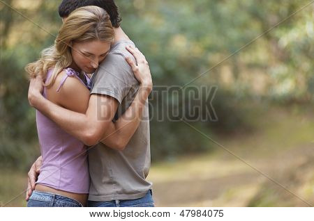 Side view of a couple standing on forest trail and hugging