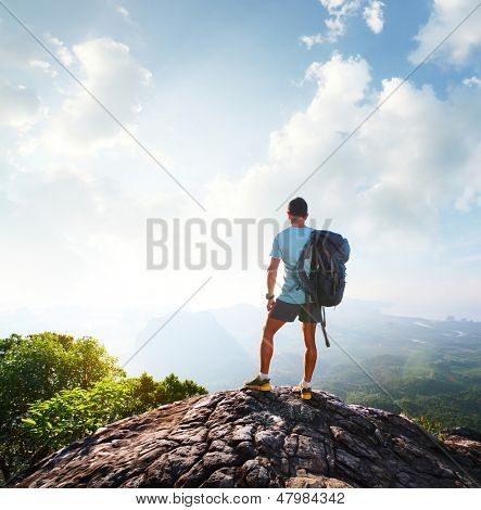 Hiker with backpack enjoying sunrise from top of a mountain