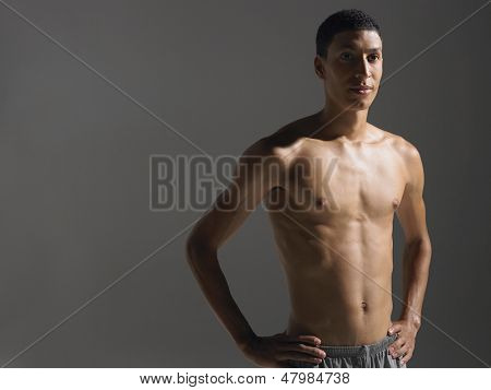 Portrait of a shirtless confident young athlete standing against gray background