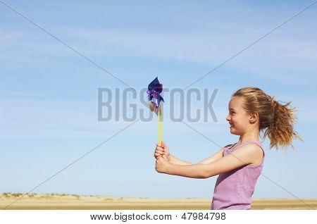 Side view of a little girl standing on windy beach with pinwheel against sky