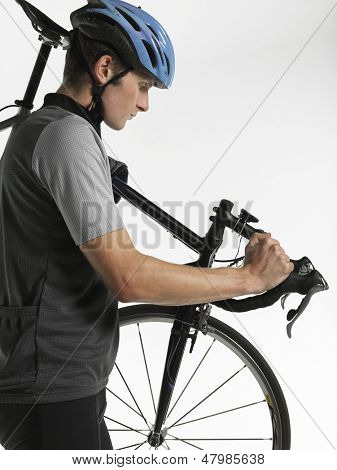 Side view of a male bicyclist carrying bicycle against white background