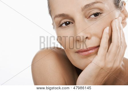 Nahaufnahme des entspannten middle aged Woman mit Hand am Kinn over white background