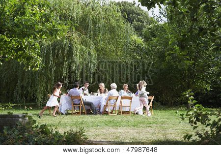 Happy family sitting at dining table while girls running around in garden