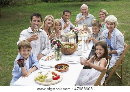 Portrait of three generation family dining together in garden
