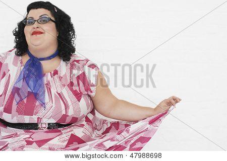 Retrato de uma mulher com excesso de peso curtseying contra um fundo branco