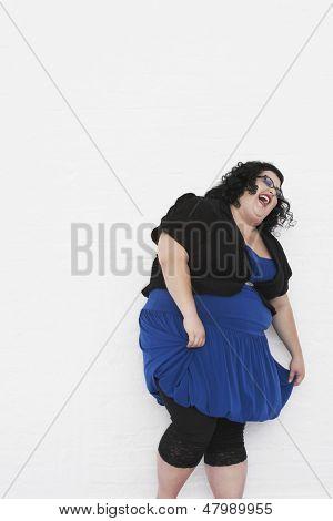 Mulher com sobrepeso, rindo enquanto curtseying contra um fundo branco