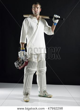 Full length of a cricket player holding bat on shoulder against black background