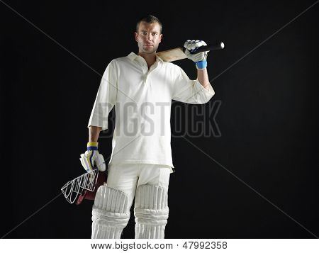 Portrait of a cricket player holding bat and helmet against black background