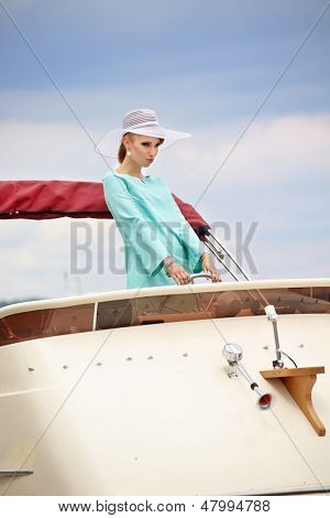 woman with steering wheel showing thumb up on the yacht