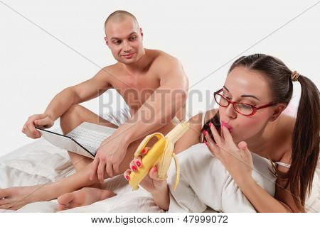 Young woman lying on bed with banana and her boyfriend  is busy with laptop