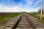 stock photo of railroad-sign  - railroad track with a rail crossing sign in countryside