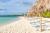 Umbrellas and out of focus people at a beach in Cayo Coco (Coco key), a natural tourist destination in Cuba poster