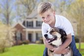 stock photo of youngster  - Happy Young Boy and His Dog in Front Yard of Their House - JPG