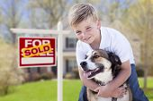stock photo of yard sale  - Happy Young Boy and His Dog in Front of Sold For Sale Real Estate Sign and House - JPG