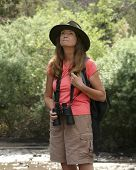 picture of khakis  - An Attractive Woman Watches Birds on a Lush Riverbank - JPG