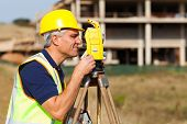 image of theodolite  - Senior land surveyor working with theodolite at construction site - JPG