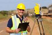 stock photo of land development  - senior land surveyor working at road construction site - JPG