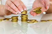 stock photo of revenue  - a woman stacks coins - JPG