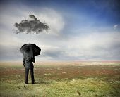 stock photo of fail job  - Crisis concept with businessman under a black cloud - JPG