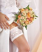 stock photo of garter  - Garter at leg of bride and flower bouquet - JPG