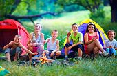 stock photo of boys night out  - group of happy kids roasting marshmallows on campfire - JPG