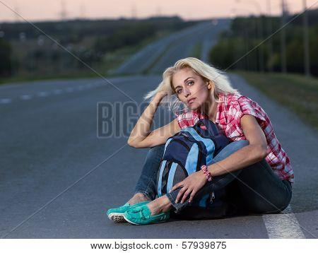 Woman With Haversack Sitting On The Road