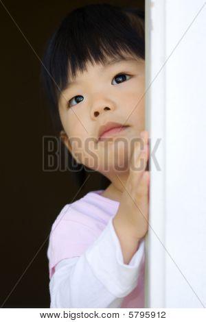 Pretty Little Child Stands Behind A Door