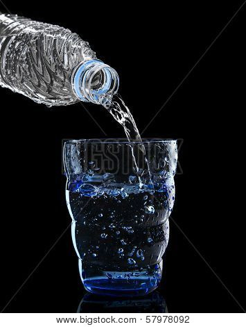 Freshness Cool And Clean Drinking Water Pouring To Blue Glass Isolated On Black Background Use For H