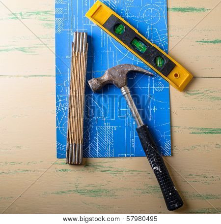 Hammer With Lostock And Folding Rule Over A Blueprint Och A Wood Table