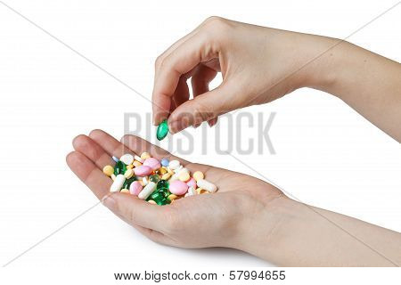 womens hands holding colored pills