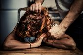 image of ginger man  - Man is Physically Abusing His Girlfriend who is sitting at a table in the kitchen - JPG