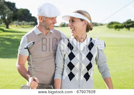 Golfing couple smiling at each other on the putting green on a sunny day at the golf course