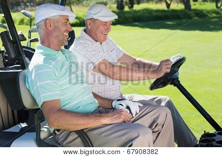 Golfing friends laughing together in their golf buggy on a sunny day at the golf course