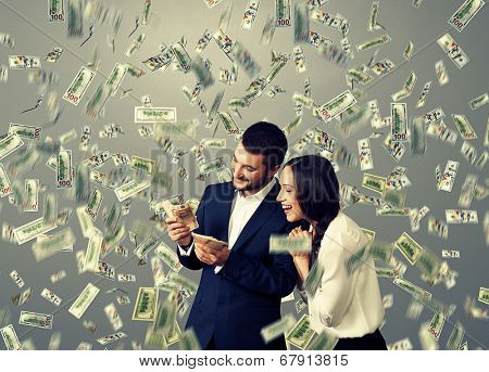 happy excited couple with money standing under dollar's rain