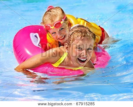 Children wearing life jacket in swimming pool.