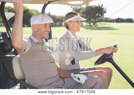 Happy golfing couple smiling in their buggy on a sunny day at the golf course
