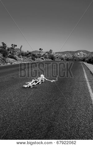 A lost hiker dies of thirst on a deserted desert road inches away from a bottle of water.  Dark Humor Series. In Black and White