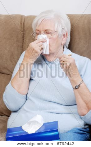 Sick Senior With Thermometer Blowing Her Nose