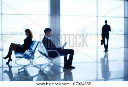Two business partners reading at the airport while their colleague standing by the window