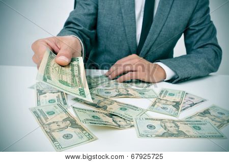 man in suit sitting in a desk full of dollar bills offering one of them to the observer