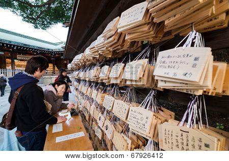Tokyo, Japan - November 23, 2013 : People Writting Ema Plaques At A Meiji Jingu Shrine, Tokyo, Japan
