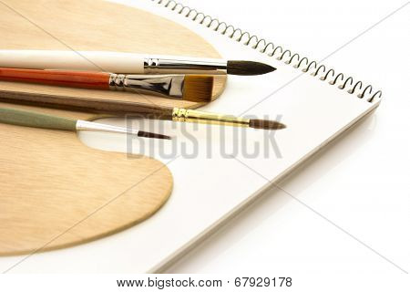 Art brushes with wooden palette and clear sketchbook isolated on white background