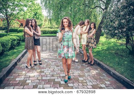 joyful girl with the mobile phone and group of envying girls