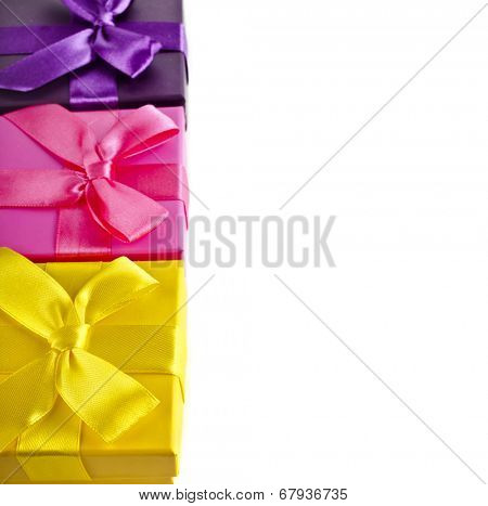 Border row of colorful gift boxes wrapped ribbon bows surface close up isolated on white background